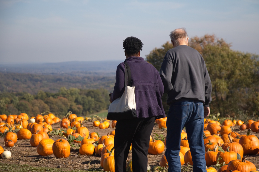 Couple preventing back pain while walking through pumpkin patch