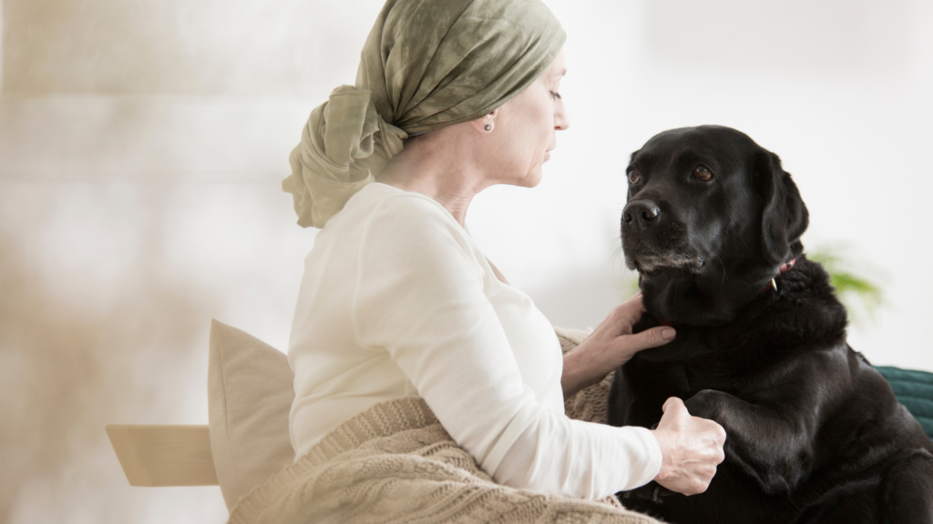 woman with cancer pain and black dog
